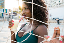 Gorgeous Black Woman With Drink Behind Net