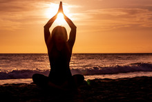 Woman Practicing Yoga On A Maui Beach At Sunset