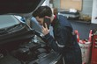 Mechanic talking on a mobile phone while examining car