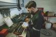 Mechanic using digital tablet at work bench