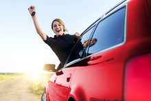 An Attractive Woman In The Red Car Holds A Car Key In Her Hand.