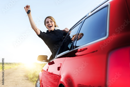 Fototapeta An attractive woman in the red car holds a car key in her hand. obraz