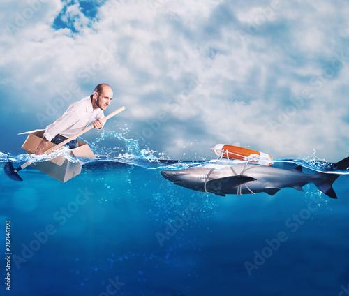Fotografía  Businessman on a cardbox in the ocean looks for an help
