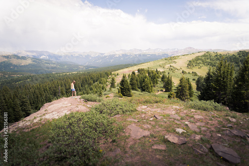 Fotobehang Wit A woman standing on a rock looking out at a mountainous, Colorado landscape.