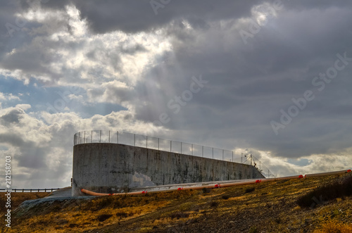 Foto op Plexiglas Stadion Concrete dam spillway with stormy skies