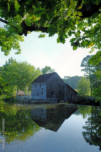 Photo  A summertime view from across the pond of the old gristmill at Historic Yates Mi