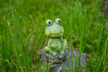 Decorative Miniature Frog.Small Funny Frog Statue In The Grass In Garden. Copy Space.Green Ceramic Figure Of A Green Frog. Decorative Elements.