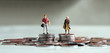 canvas print picture - A miniature man and a miniature woman standing on top of a pile of coins of the same height.