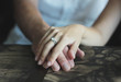 Woman's hand with an engagement ring on man's hand, date in the cafe