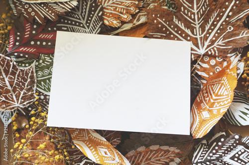 White paper card on a background of dry patterned leaves. Empty space for your design.