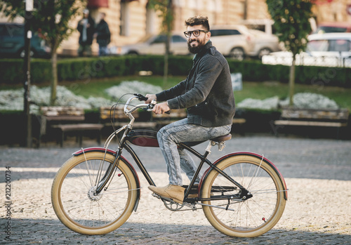 Fotografie, Obraz  Bearded Smiling Young Man in Glasses Riding Bike.