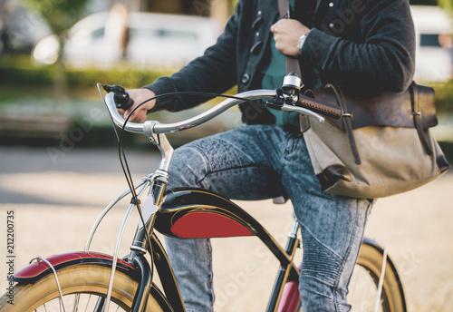 Fotografie, Obraz  Young Man in Jeans Pants with Bag Riding Bike.