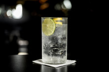 Close Up Of Glass Of A Freshly Prepared Gin And Tonic With Lime Slices And Twist Of Lemon, Isolated.