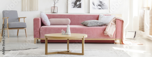 Pink sofa with patterned pillows and wooden coffee table with armchair and painting in the background in a modern living room interior