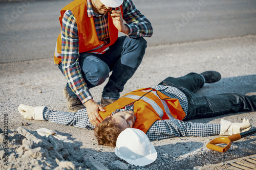 Fotografía  Worried man calling ambulance for his unconscious coworker