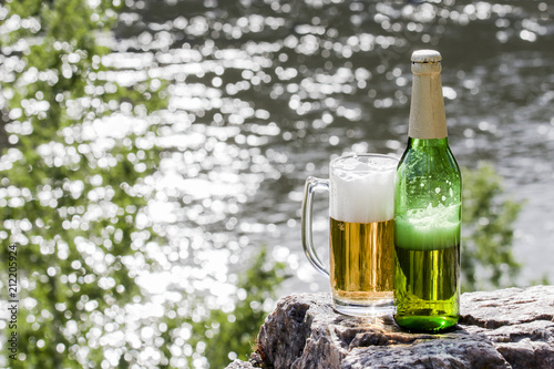 Foto op Aluminium Bier / Cider Bottle and mug of beer stands on a rock at the river