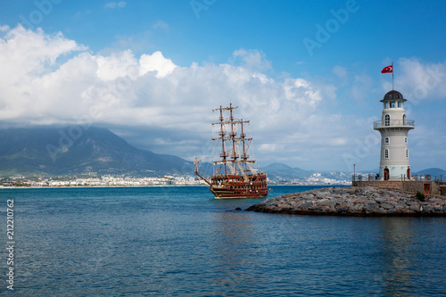 Spoed Foto op Canvas Schip medieval wooden ship and lighthouse in Turkey
