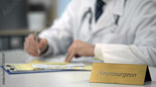 Fototapeta Neurosurgeon typing medical records on laptop, completing monthly reports