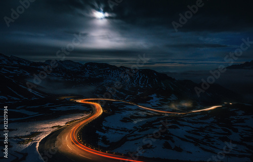 Fotografia The winding mountain High Alpine Road Pass at night with light tracks from cars,