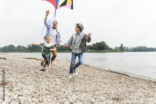Happy father with two sons flying kite at the riverside
