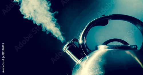 Valokuva  Kettle whistling, boiling kettle with steam texture on a black background