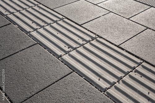 Valokuvatapetti Line of hazard warning tactile paving along the edge of platform at the train station