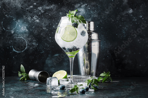Summer alcoholic cocktail blueberry mojito with rum, mint, lime and ice, bar tools, gray background, selective focus