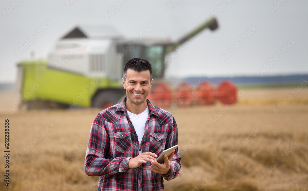 Fototapety, obrazy: Farmer with tablet in field during harvest