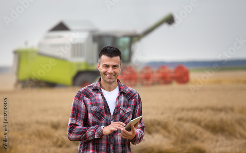 Fototapeta Farmer with tablet in field during harvest obraz