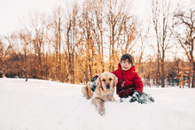 Boy Sitting In The Snow With His Golden Retriever Dog