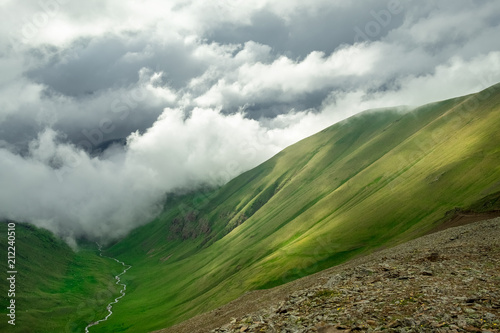 mountain valley and mountain peaks with the remains of snow on the slopes closed by low dense clouds landscape illustration background