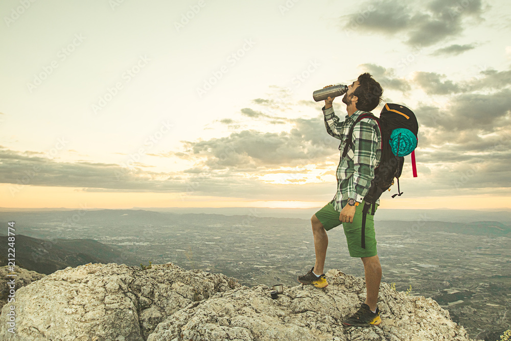 Fototapety, obrazy: Guy drinking water in the mountains .Hiker drinking water