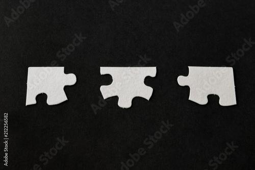 Fotografie, Obraz  White jigsaw puzzle pieces on black background;