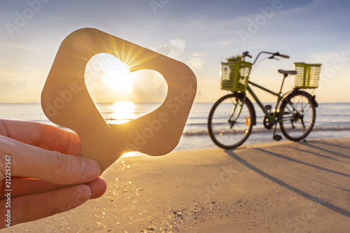 Fotobehang Fiets Like icon in a man hand bicycle trip beach sunrise