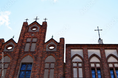 Foto op Aluminium Oude gebouw Fragment of old historical red brick church building facade with decorative details and cross on light sky background close up view.