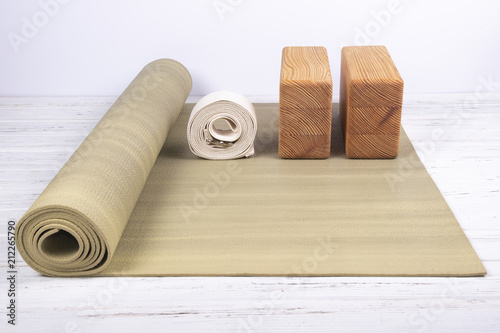 Composition of yoga, meditation or pilates accessories on white wooden background.