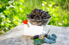 Juicy Summer Berries In A Glass. Black Delicious Juicy Mulberry On The Background Of The Garden. Copy Space