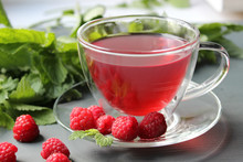 Transparent Cup Of Fragrant Tea With Addition Of Berries Of A Raspberry On A Dark Background, The Scattered Around Twigs Of Raspberry And Mint Leaves