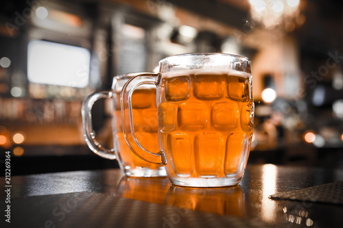Foto op Plexiglas Bier / Cider Two glass mugs of cold bar in a typical Irish pub setting