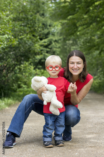Fotografia, Obraz  Mother and her cute toddler son with plush bear and toy glasses outdoor
