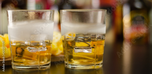 Spoed Foto op Canvas Bar glass of whiskey with ice cubes and salty snacks on the background of bottles and bar