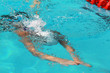 Young swimmer with white swimming cap swims breaststroke dive under water in the swimming pool for competition