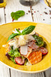Caesar salad with salmon. mix of salads, cherry tomatoes, parmesan cheese, basil. A dish in a ceramic plate is on a wooden table in a restaurant. A glass of white wine is on the table. selective focus
