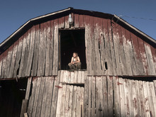 Young Blonde Girl In Camouflage Pants And Green Tank Top Crouching In Hay Loft Doorway With Eyes Closed