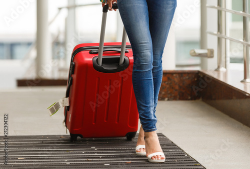Fotografija  Woman's legs and travel suitcase at international airport tax free shopping zone