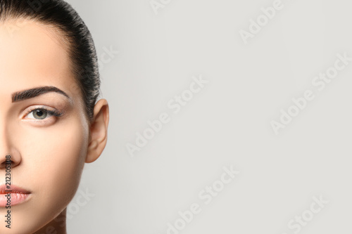 Fotografía  Young woman with permanent eyebrows makeup on grey background