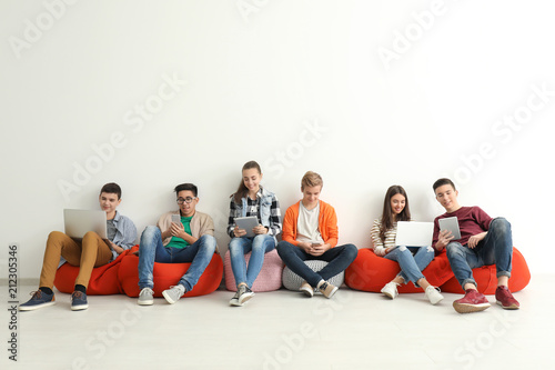 Fotografie, Obraz  Group of teenagers with modern devices sitting near white wall