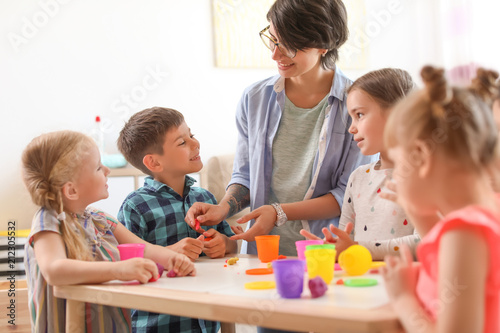 Fototapeta Young woman playing with little children indoors obraz