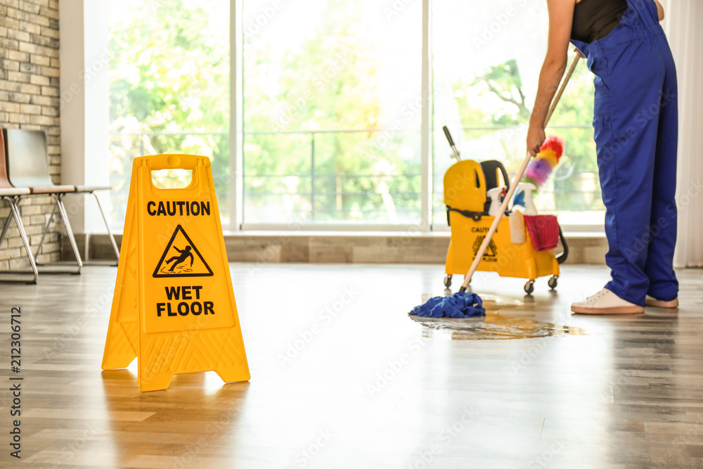 Fototapeta Safety sign with phrase Caution wet floor and cleaner indoors. Cleaning service