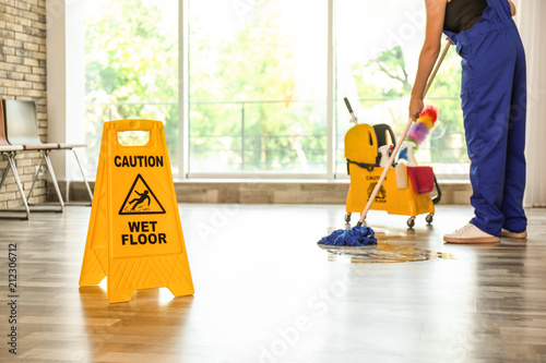 Obraz na plátne Safety sign with phrase Caution wet floor and cleaner indoors